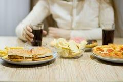 Het meisje zit bij de lijst en eet snel voedsel Stock Afbeelding