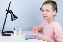 Het meisje zit bij de lijst en zet op een contactlens om visie te verbeteren royalty-vrije stock afbeeldingen