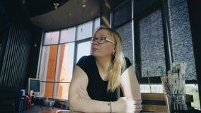 Het meisje zit bij de lijst in het restaurant wachtend op de voorbereiding van haar orde Zij kijkt weg stock footage