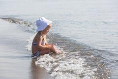 Het meisje zit bij de rand van het water royalty-vrije stock afbeelding