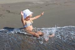Het meisje zit bij de rand van het water royalty-vrije stock fotografie