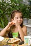 Het meisje zit bij een lijst met maaltijd en eet Royalty-vrije Stock Afbeelding