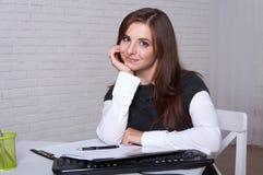Het meisje zit bij een werkstation propped haar hoofd op haar hand royalty-vrije stock foto