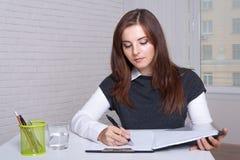 Het meisje zit bij een werkstation schrijft in de documentomslag stock foto's