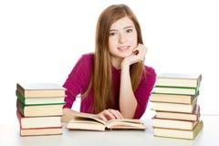 Het meisje zit bij het bureau en leest boek Royalty-vrije Stock Afbeeldingen