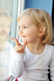 Het meisje zit bij venster stock fotografie