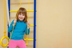 Het meisje zit cheerfully op een sportenladder royalty-vrije stock foto's