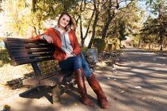 Het meisje zit in de herfst op een bank in het park Stock Afbeelding