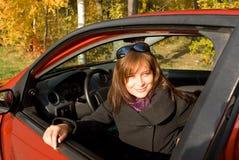 Het meisje zit in de rode auto Stock Afbeeldingen
