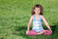 Het meisje zit in de schaduw in asana op gras Royalty-vrije Stock Foto