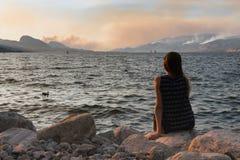 Het meisje zit door lakeshore in Marine Park die in Penticton op veelvoudige verlichting gevonkte wildfires in Zuiden Okanagan le stock foto's