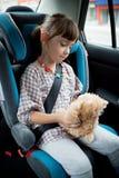 Het meisje zit in een auto Stock Afbeelding
