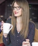 Het meisje zit in een een bar en het drinken thee stock afbeelding