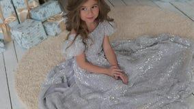 Het meisje zit in een mooie glanzende kleding Kerstmisbinnenland stock videobeelden