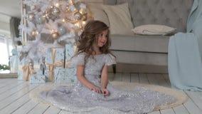 Het meisje zit in een mooie glanzende kleding Kerstmisbinnenland stock video