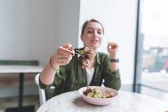 het meisje zit in een restaurant dichtbij het venster en leidt een vork met een salade aan de camera royalty-vrije stock foto's