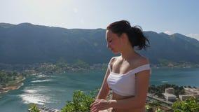 Het meisje zit en rust bij hoge hoogte in de bergen stock videobeelden