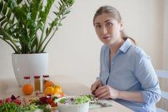 Het meisje zit en snijdt groenten Stock Afbeelding