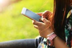 Het meisje zit En speel een smartphone in een tuin Goed weer stock foto