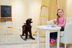 Het meisje zit in grote leunstoel en bekijkt boek Stock Foto's