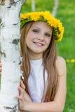 Het meisje zit in het gras met kroon van paardebloemen op haar h Stock Foto's