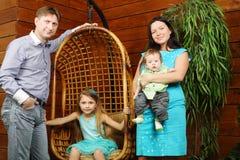 Het meisje zit in het hangen van stoel en vader, moeder met baby royalty-vrije stock fotografie