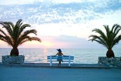 Het meisje zit het wachten door het overzees Stock Foto
