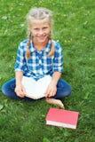 Het meisje zit lezing op het gras stock afbeelding