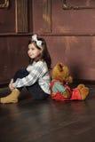 Het meisje zit met de beer Stock Afbeelding
