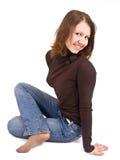Het meisje zit met de benen over elkaar Stock Afbeeldingen