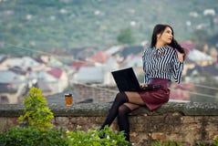Het meisje zit met laptop in de aard Stock Foto