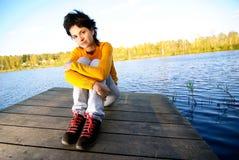 Het meisje zit op brug Royalty-vrije Stock Fotografie