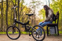 Het meisje zit op de bank en er is een fiets voor haar stock afbeeldingen