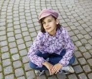 Het meisje zit op de bestrating Royalty-vrije Stock Foto's