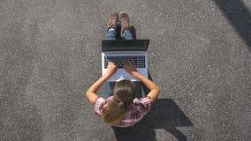 Het meisje zit op de bestrating met laptop stock videobeelden