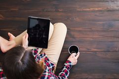 Het meisje zit op de houten vloer met een kop van koffie in haar handen en leest het nieuws in de tablet stock foto's