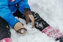 Het meisje zit op de sneeuw in de winter stock foto's