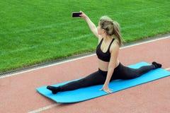 Het meisje zit op de spleten De jonge mooie vrouw met een mobiele telefoon in haar hand doet selfie tijdens gymnastiek- oefeninge royalty-vrije stock foto's
