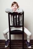 Het meisje zit op de stoel, het glimlachen Stock Afbeelding