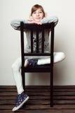 Het meisje zit op de stoel, het glimlachen Stock Afbeeldingen