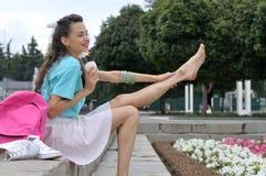 Het meisje zit op de treden houdend haar been stock foto