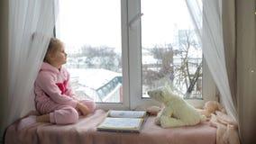 Het meisje zit op de vensterbank en kijkt stock footage