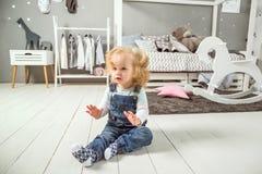 Het meisje zit op de vloer in haar ruimte stock afbeeldingen