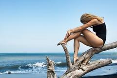 Het meisje zit op dode boomtak op zwart strand stock fotografie
