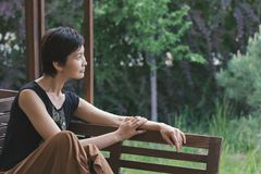 Het meisje zit op een bank en kijkt zorgvuldig in de afstand Vrouwendromen ontspan stock foto