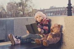 Het meisje zit op een bank en leest het boek aan een stuk speelgoed draagt Royalty-vrije Stock Foto's