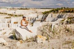 Het meisje zit op een brok van marmer, mening van marmeren steengroeve Stock Afbeeldingen