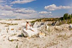 Het meisje zit op een brok van marmer, mening van marmeren steengroeve Stock Fotografie