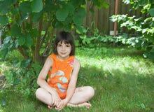 Het meisje zit op een gras onder een struik Royalty-vrije Stock Afbeeldingen