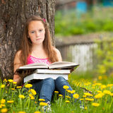 Het meisje zit op een gras terwijl het lezen van een boek Royalty-vrije Stock Afbeeldingen